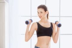 Young woman weight loss perfect body shape. Young female weight loss standing in the kitchen holding dumbbells Stock Images