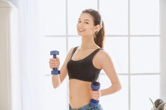 Young woman weight loss perfect body shape. Young female weight loss standing in the kitchen holding dumbbells Royalty Free Stock Photography