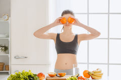 Young woman weight loss perfect body shape. Young female weight loss standing in the kitchen playful Royalty Free Stock Images