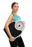 Young woman with a weight scale Royalty Free Stock Image