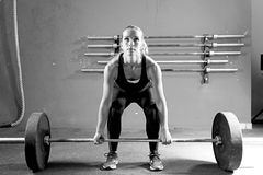 Young woman on a weightlifting session - crossfit workout. Female athlete is preparing to lift deadlift at the crossfit box - focus on the woman royalty free stock images