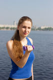 Young woman with weights exercising in the nature. Healthy lifestyle and fitness concept Stock Photo