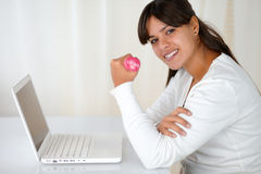 Young woman with weights in front of laptop Royalty Free Stock Image