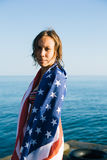 Young woman with wet hair in american flag on pier Royalty Free Stock Image