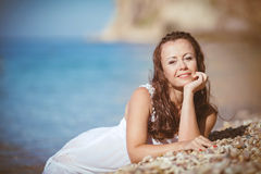 Young woman with wet hair lying near the sea Stock Photo