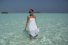 Young woman in a wet white dress standing in turquise water. Young woman in a wet white dress standing in the water near the Maldive Islands Royalty Free Stock Photo