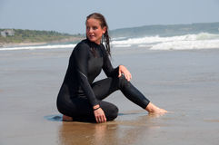 Young Woman in a Wetsuit at Beach. A young woman kneels by the shoreline in her wetsuit at the beach Royalty Free Stock Image