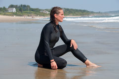 Young Woman in a Wetsuit at Beach. A young woman sits by the shoreline in her wetsuit at the beach Royalty Free Stock Images