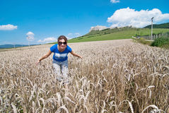 Young woman in wheat field, back is Spis castle. Young woman in sunglasses in wheat field, back is Spis castle royalty free stock image