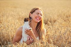 Young woman in wheat field, lit by afternoon sun, trying to pose stock photography