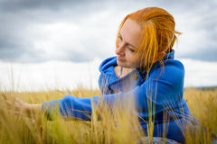 Young woman in wheat field. Young woman wearing blue sweater in wheat field on a cloudy day Stock Images