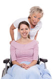 Young woman in wheelchair, aged nurse Stock Photos