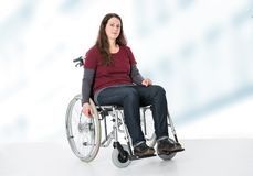 Young woman in wheelchair. In front of bright  background Royalty Free Stock Image