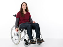 Young woman in wheelchair. In front of white background Stock Photo