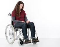 Young woman in wheelchair. In front of white background Royalty Free Stock Photos