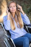 Young woman in wheelchair listening to music Stock Photos