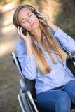 Young woman wheelchair listening to music royalty free stock images
