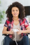 Young woman in wheelchair playing video games at home royalty free stock photos