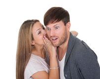 Young woman whispered something. Young women whispered something naughty in man's ear stock images