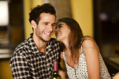 Young woman whispering into her boyfriend's ear. Young women whispering into her boyfriend's ear at dinner Royalty Free Stock Image