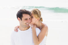 Young woman whispering in mans ears on the beach Royalty Free Stock Photography