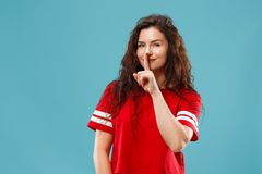 The young woman whispering a secret behind her hand over blue background. Secret, gossip concept. Young woman whispering a secret behind her hand. Business woman stock photo