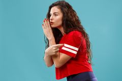 The young woman whispering a secret behind her hand over blue background. Secret, gossip concept. Young woman whispering a secret behind her hand. Business woman royalty free stock photo