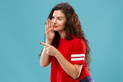 The young woman whispering a secret behind her hand over blue background. Secret, gossip concept. Young woman whispering a secret behind her hand. Business woman royalty free stock image