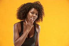 The young woman whispering a secret behind her hand. Secret, gossip concept. Young woman whispering a secret behind her hand. Business woman isolated on trendy royalty free stock photo