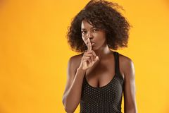 The young woman whispering a secret behind her hand. Secret, gossip concept. Young woman whispering a secret behind her hand. Business woman isolated on trendy royalty free stock image