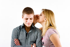 Young woman whispering a secret. Young women whispering a secret to a man's ear Stock Image