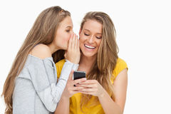 Young woman whispering to her friend who's texting on her phone Stock Photography