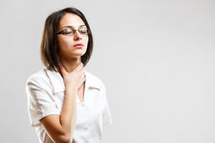 Young woman whit sore throat. In gray background Stock Image