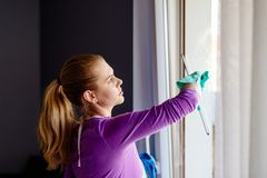 Young woman in white apron cleaning windows. royalty free stock photos
