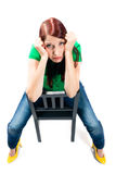 Young woman with white background being bored. Woman is sitting on a Chair in the Studio and is demotivated or frustrated, even clueless or bored stock photo