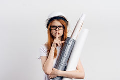 Young woman on white  background with glasses holding blueprints, engineer, building, blank space for copy.  Royalty Free Stock Photo