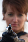 Young woman on a white background to aim a pistol Stock Images
