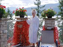 Young Woman in White Bath Robe  Relaxing by Outdoor Pool. Halcyon Hot Springs, British Columbia, Canada Royalty Free Stock Photography