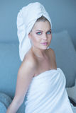Young Woman in White Bath Towel Sitting on Sofa Stock Images