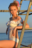 Young woman in a white bathing suit on a background of a sea lan. Beautiful girl model in swimsuit sitting on a background of sea and sky Stock Photo