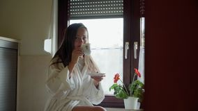 Young woman in white bathrobe drinks coffee or tea and sitting on the stone table in the cozy kitchen at the morning. Coffee break. Close up of woman legs in stock video footage