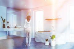 Young woman in white bathroom corner. Rear view of woman in pajamas standing in comfortable bathroom with white walls, double sink and white bathtub. Toned image royalty free stock photography