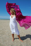 Young woman in white on beach with red fluttering royalty free stock photos