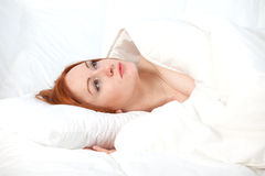 Young woman in white bedding Stock Photos