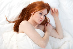 Young woman in white bedding Stock Image