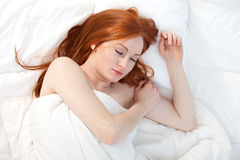 Young woman in white bedding Royalty Free Stock Photo