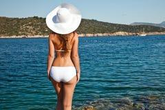 Young woman in white bikini. Looking at sea Royalty Free Stock Image