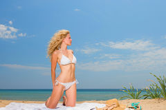 Young woman in white bikini holding sarong on the beach Royalty Free Stock Photography
