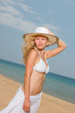 Young woman in white bikini holding sarong on the beach Stock Photography