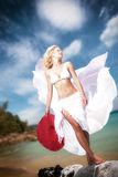 Young woman in white bikini holding sarong on the beach Stock Images
